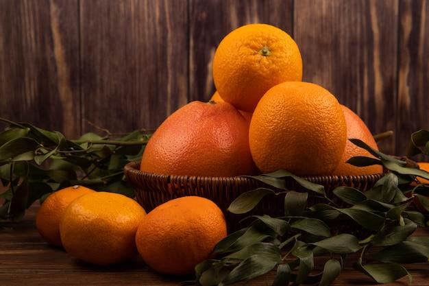 Vista lateral de laranjas frescas maduras em uma cesta de vime e folhas verdes em madeira escura
