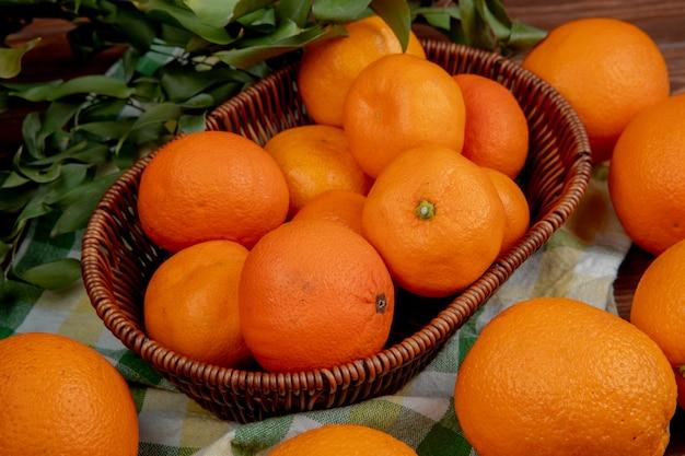 Vista lateral de laranjas frescas maduras em uma cesta de vime na toalha de mesa xadrez