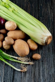 Vista lateral de legumes como batata de aipo e cebolinha em fundo de madeira com espaço de cópia