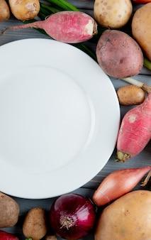 Vista lateral de legumes como batata rabanete de cebola com prato vazio