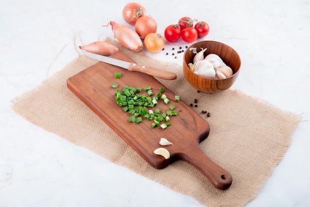 Vista lateral de legumes como cebola verde na tábua tomate alho com faca sobre fundo branco, com espaço de cópia