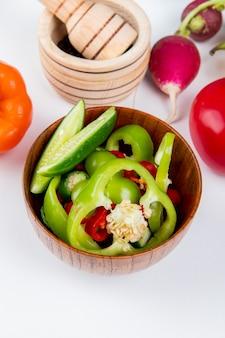 Vista lateral de legumes como fatias de pimentão e pepino com rabanete e tomate com pimenta preta no triturador de alho na mesa branca