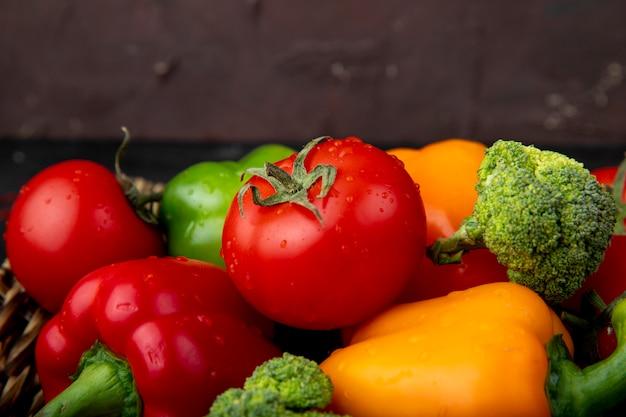 Vista lateral de legumes como tomate pimentão brócolis na superfície marrom
