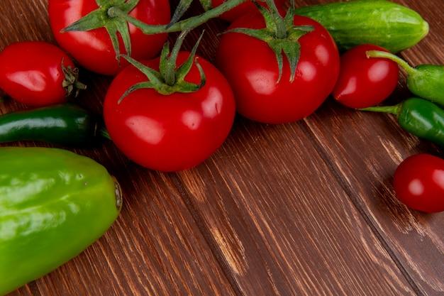 Vista lateral de legumes frescos tomates maduros pepinos pimenta e pimentão colorido na mesa rústica de madeira