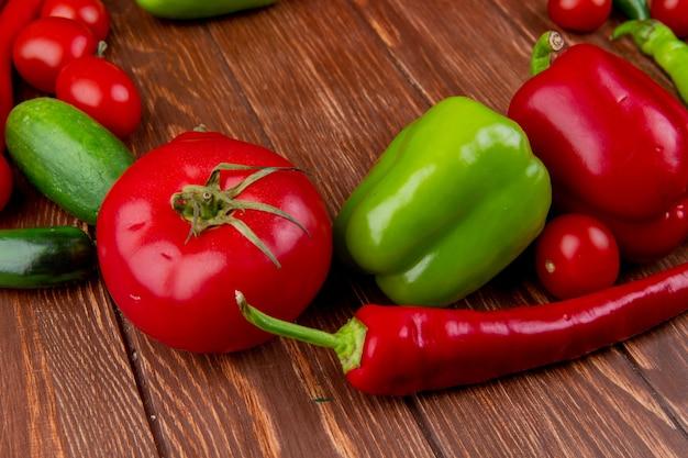 Vista lateral de legumes frescos tomates maduros pepinos pimenta vermelha e pimentões coloridos em madeira rústica