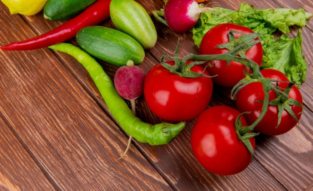 Vista lateral de legumes frescos tomates maduros pepinos verde pimenta e rabanete na madeira rústica