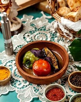 Vista lateral de legumes recheados com carne e arroz em uma tigela de barro