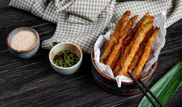 Vista lateral de legumes tempura em uma tigela servida com molho de soja na mesa de madeira com tecido xadrez