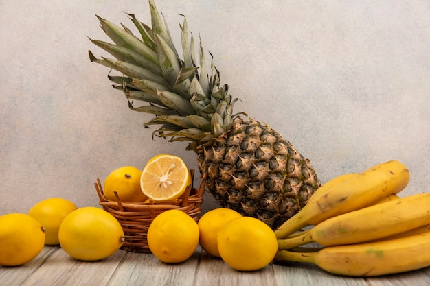 Vista lateral de limões amarelos em um balde com bananas e abacaxi, isolados em uma mesa de madeira cinza sobre uma superfície branca