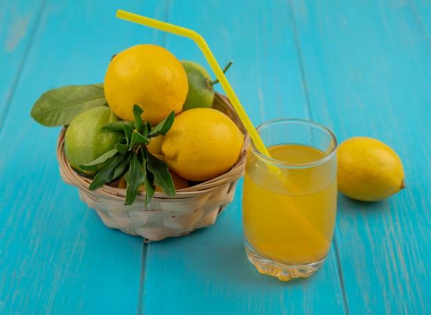 Vista lateral de limões e limas em uma cesta e um copo de suco de limão em um fundo turquesa