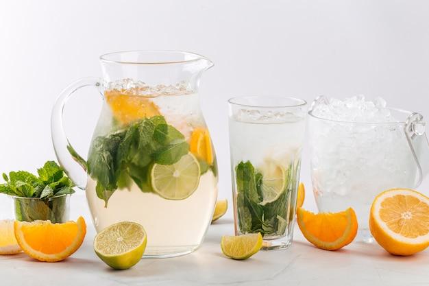 Vista lateral de limonada de laranja e limão em uma jarra e vidro isolado