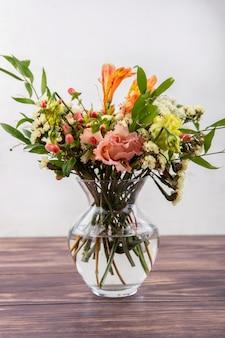 Vista lateral de lindas flores coloridas diferentes com folhas em um vaso de vidro em uma mesa de madeira na superfície branca