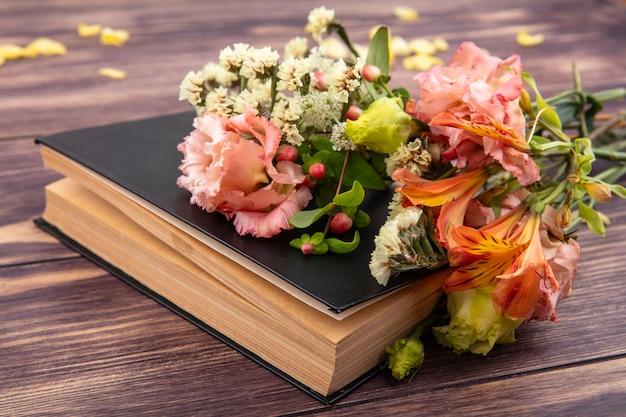 Vista lateral de lindas flores coloridas e diferentes com folhas em uma superfície de madeira