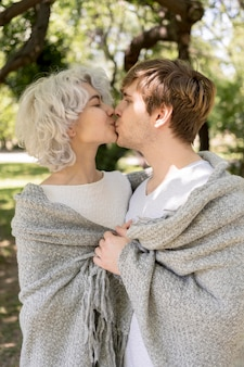 Vista lateral de lindo casal coberto de cobertor se beijando ao ar livre