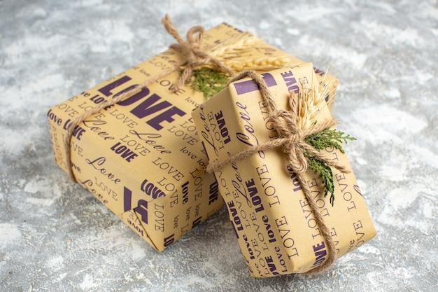 Vista lateral de lindos presentes embalados de natal com inscrição de amor na mesa de gelo