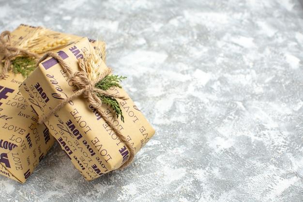 Vista lateral de lindos presentes embalados de natal com inscrição de amor no lado direito na mesa de gelo