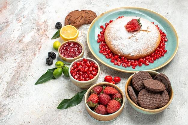 Vista lateral de longe bagas e biscoitos geleia de limão biscoitos o bolo com morangos frutas cítricas