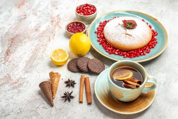 Vista lateral de longe bolo com morangos uma xícara de chá o bolo ao lado das bagas de limão