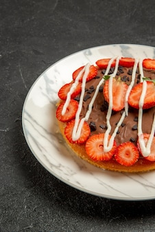 Vista lateral de longe bolo sobre a mesa bolo com morangos e chocolate no lado direito da mesa preta