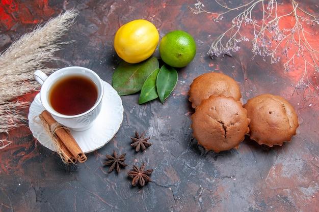 Vista lateral de longe bolo uma xícara de chá com bolinhos de canela frutas cítricas anis estrelado