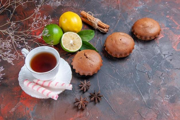 Vista lateral de longe frutas cítricas frutas cítricas uma xícara de chá cupcake anis estrelado canela