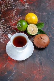Vista lateral de longe frutas cítricas, limões, cupcake, uma xícara de chá