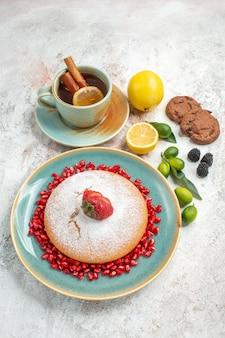 Vista lateral de longe o apetitoso bolo uma xícara de chá com biscoitos de chocolate com limão e um bolo com romã e morangos
