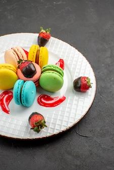 Vista lateral de longe prato de macaroons coloridos de molho de macaroons verde amarelo azul e rosa e apetitosos morangos cobertos de chocolate na mesa escura
