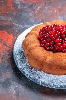 Vista lateral de longe saboroso bolo de bolo com frutas no prato na superfície vermelho-azul