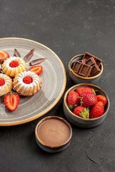 Vista lateral de longe taças de chocolate e biscoitos de chocolate, morangos e creme de chocolate ao lado do prato de biscoitos com morangos na mesa