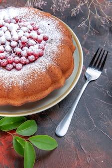 Vista lateral de longe um bolo apetitoso bolo com folhas de frutas silvestres e garfo
