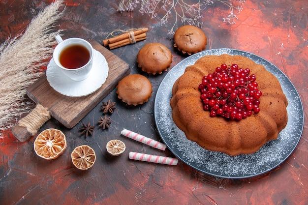 Vista lateral de longe um bolo um bolo com frutas vermelhas doces de limão uma xícara de chá no tabuleiro