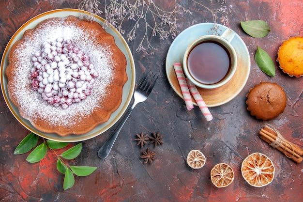 Vista lateral de longe um bolo um bolo com frutas vermelhas folhas doces bolinhos uma xícara de chá frutas cítricas