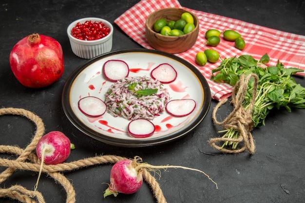 Vista lateral de longe um prato um prato de frutas cítricas de romã verdes avermelhadas