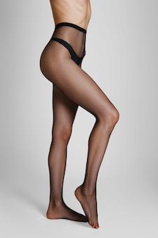 Vista lateral, de, longo, excitado, femininas, pernas, em, fishnet, calças justas, com, uma perna, dobrado, em, joelho, e, ligado, tiptoe