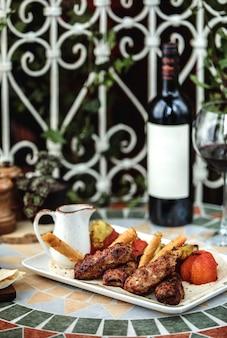 Vista lateral de lula kebab com tomate frito em cima da mesa