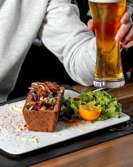 Vista lateral de lulas fritas e polvo com queijo e batatas e um pão na mesa