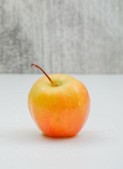 Vista lateral de maçã chuvosa única em um branco