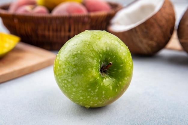 Vista lateral de maçã verde e fresca com pêssegos em um balde e meio coco na superfície branca