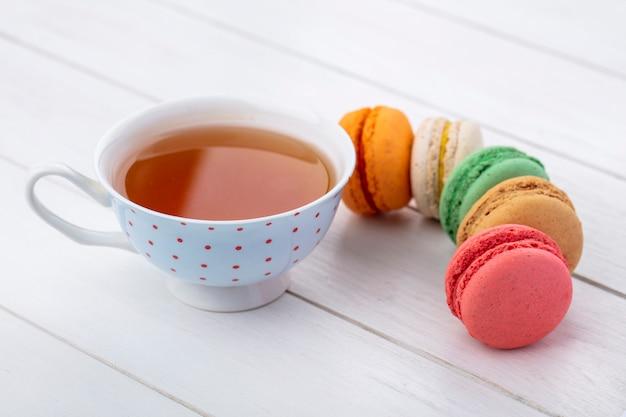 Vista lateral de macarons multicoloridos com uma xícara de chá em uma superfície branca