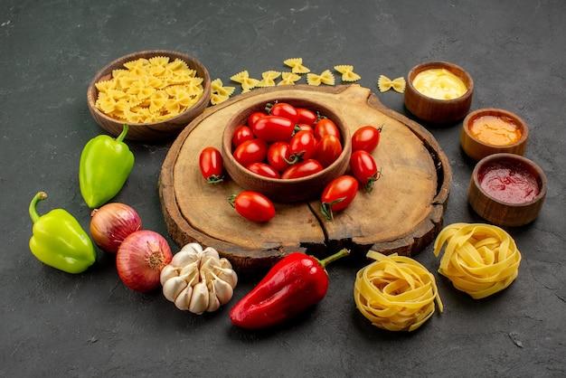 Vista lateral de macarrão com especiarias macarrão com três tipos de molho alho cebola pimentão vermelho e verde ao lado da tigela de tomates na tábua de madeira