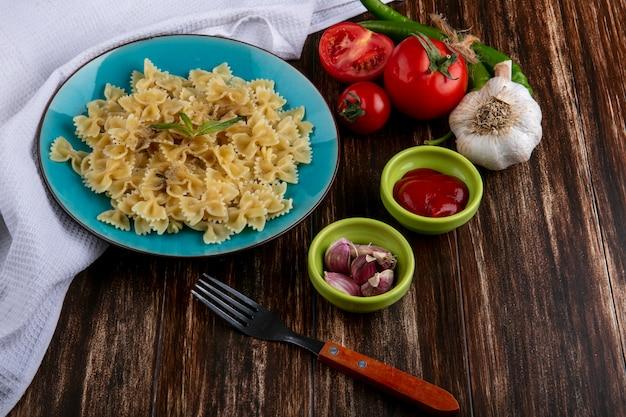 Vista lateral de macarrão cozido em um prato azul com um garfo, tomate ketchup e pimenta em uma superfície de madeira