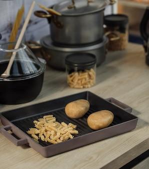 Vista lateral de macarrão espiral cru e duas batatas em uma panela em uma mesa de cozinha