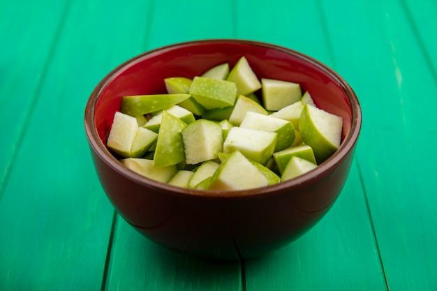 Vista lateral de maçãs picadas na tigela vermelha na superfície verde