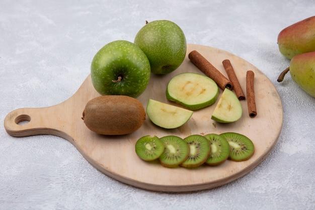 Vista lateral de maçãs verdes com fatias de kiwi e canela em um suporte sobre fundo branco