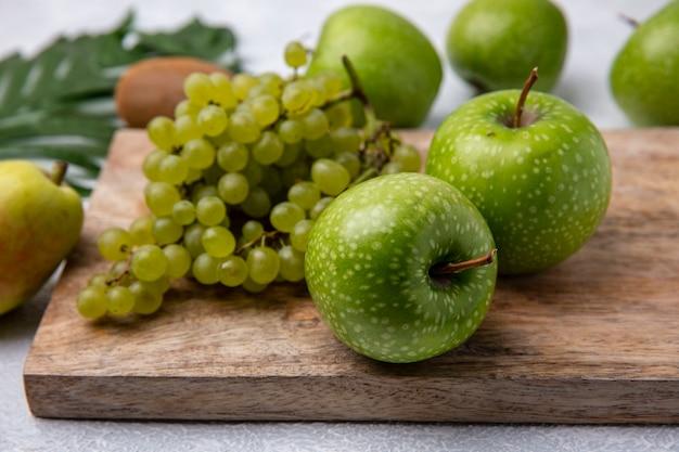 Vista lateral de maçãs verdes com uvas verdes em um suporte em um fundo branco