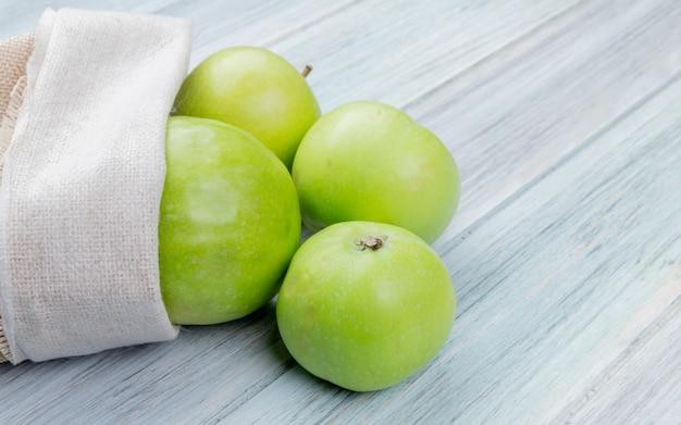 Vista lateral de maçãs verdes, derramando fora do saco na superfície de madeira com espaço de cópia