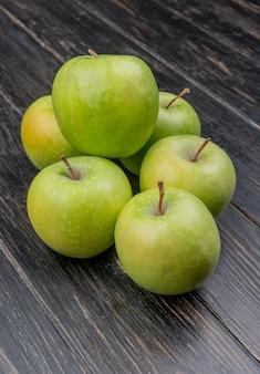 Vista lateral de maçãs verdes em fundo de madeira