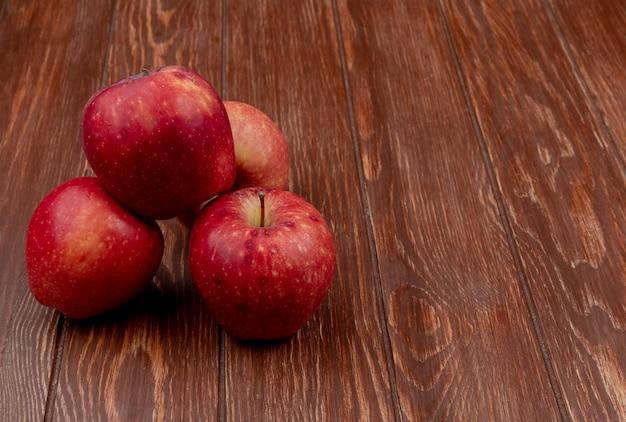 Vista lateral de maçãs vermelhas em fundo de madeira com espaço de cópia