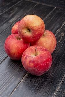 Vista lateral de maçãs vermelhas na madeira